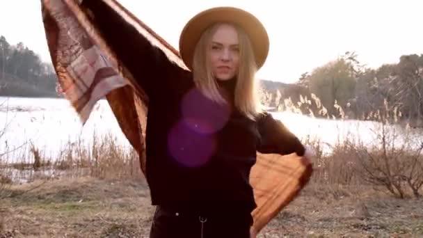 Millenniumi nő 4k kaukázusi szőke nő bézs kalapban sálat visel játszik napsugárral vidéken. Arany óra, házikó. Helyi utazás. Lassú élet. Mentális egészség