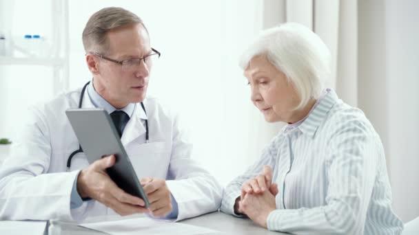 Lékařská pomoc. Lékař středního věku konzultuje se starší ženou, drží pc tablety a předepisuje léčbu svému pacientovi, sedí u stolu ve své kanceláři