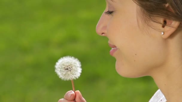 Young happy woman blows dandelion