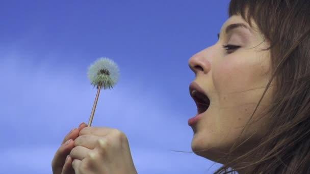 Young happy woman blows dandelion