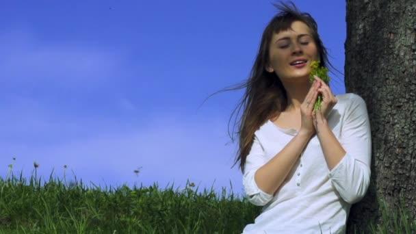 mladá žena vonící žluté květy