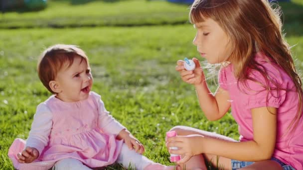 Two little girls playing on lawn
