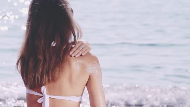 žena použití opalovacího krému na rameno