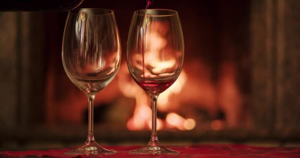 Pouring glasses of red wine by fireplace