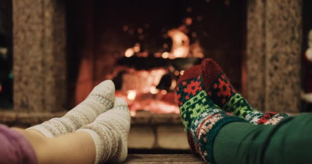 Mother and child warming feet by fireplace