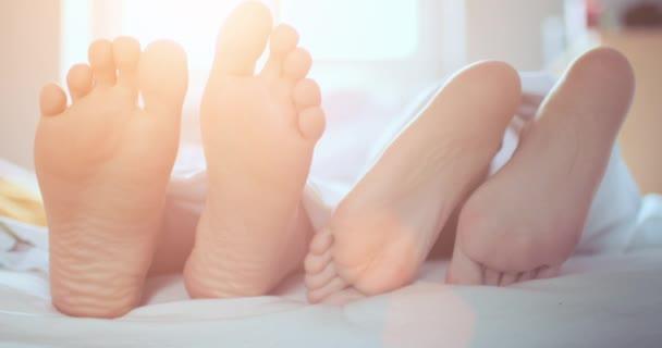 Dvojice nohou hraje dotýkání nohou pod stolem v posteli