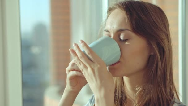 žena pití kávy oknem