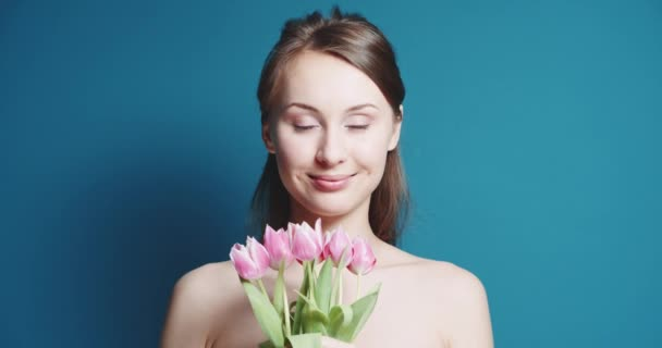 Beautiful woman with bouquet of pink tulips
