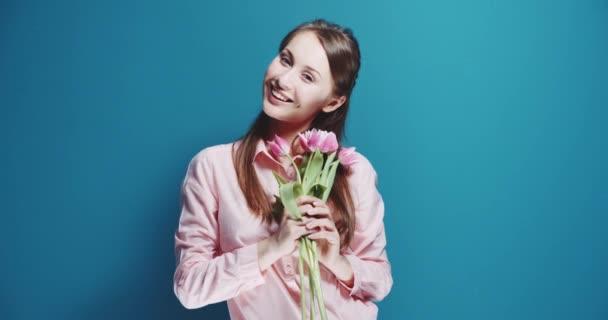 Krásná žena s kytici růžových tulipánů