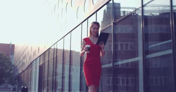 Business woman with digital tablet walking