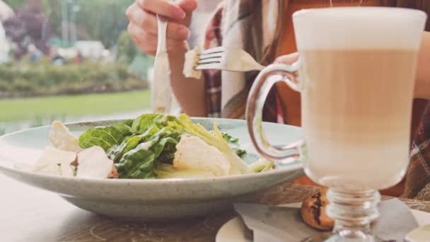 Žena jíst salát v venkovní kavárně