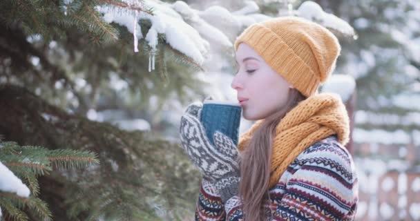 Žena pije horký čaj, venku
