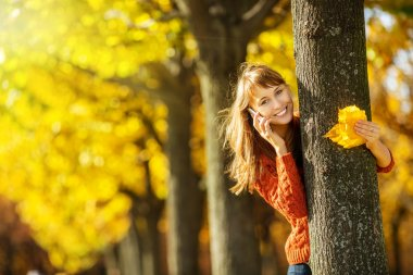 Woman talking on mobile phone in autumn park