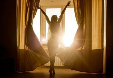 Woman  looking at sunrise standing near window