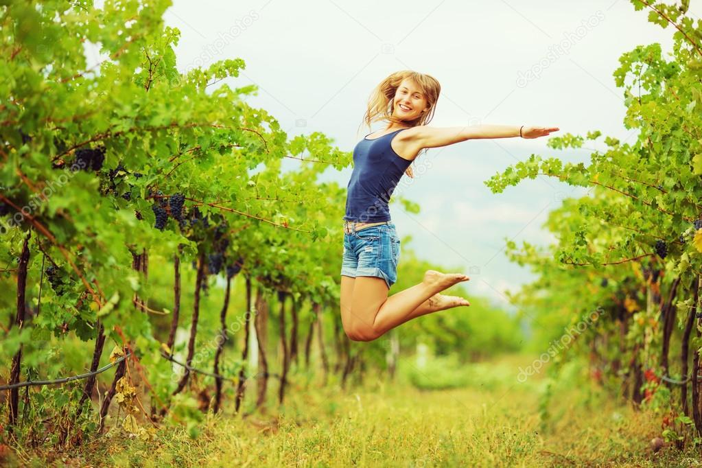 Woman jumping in  vineyard