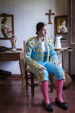 Woman Bullfighter waiting in hotel room before going to the bullring in Seville, Spain