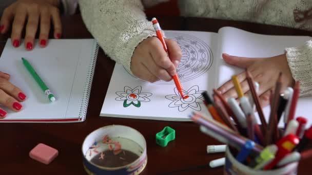 Fiatal lány festés virágok a papíron, ő anya rögzíti, hogy nem festeni a helyen kívüli