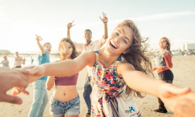 Group of friends having fun and dancing on the beach