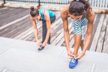 Sportive women tying shoelaces