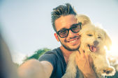 Fotografie Young man and his dog taking a selfie