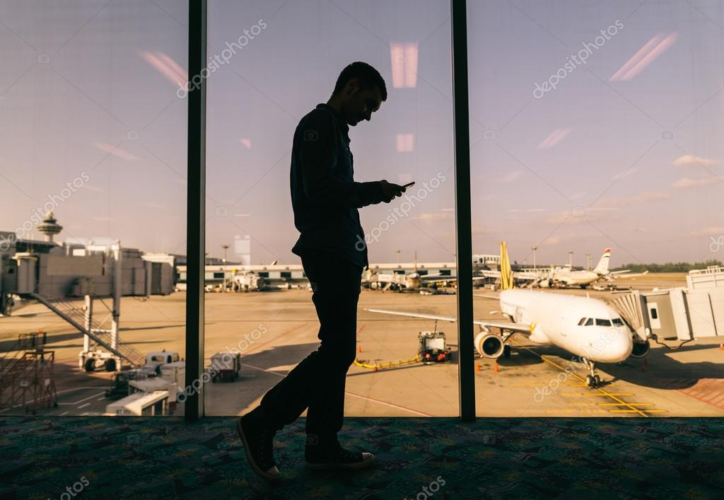 Man with smartphone at airport