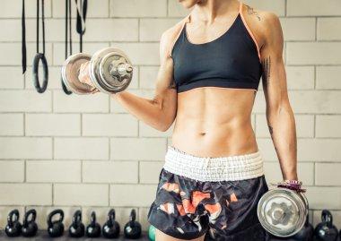Fit woman making biceps training