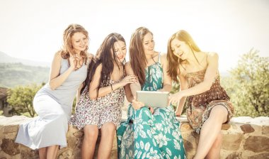 group of girls watching tablet outdoor