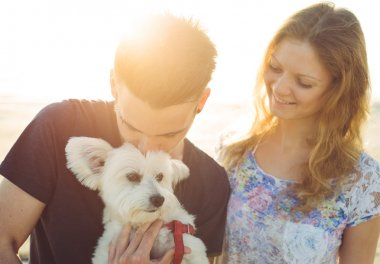 young couple and white dog happily together