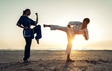 couple training in martial arts on the beach
