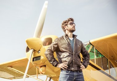 Aviator posing before flight with his aircraft. concept about airplanes,pilots and people stock vector