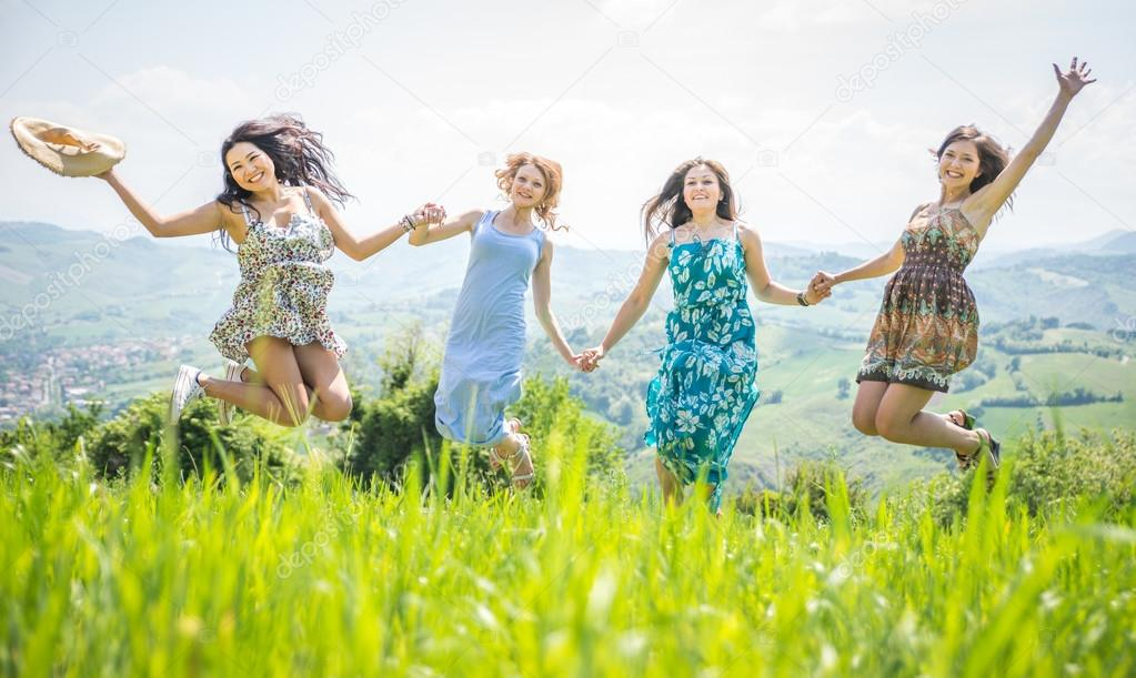 four girls jumping together in the nature