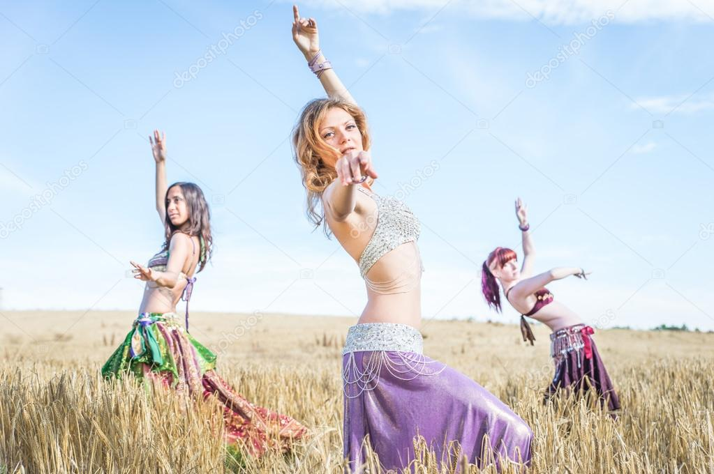 three belly dancer performing in a wheat field