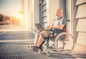Photo Man on wheel chair using computer