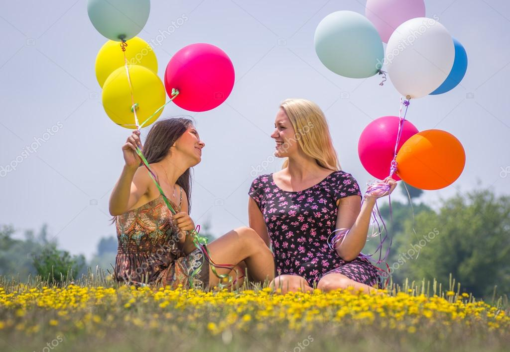 two young girls lying in the grass with air balloons