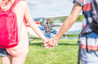 couple making an excursion on a small airplane. pilot welcomes them