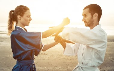 couple of martial artists training on the beach at sunrise