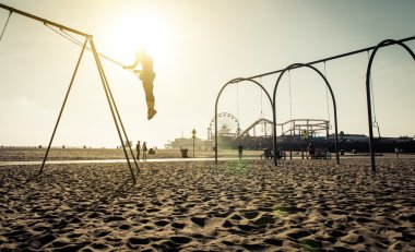 santa monica beach. silhouette of a woman going up with the swing