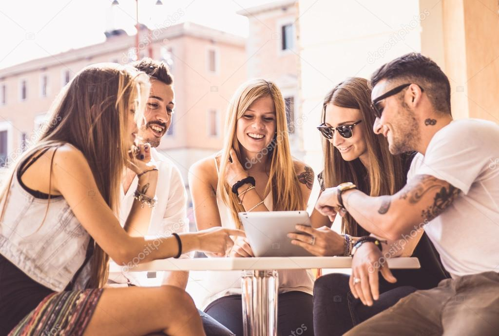 Group of friends watching tablet in a bar