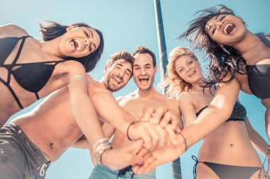 Mixed group of friends having fun on the yacht
