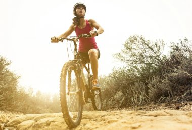 Young woman making downhill with her mountain bike