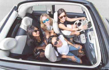 Four girls having fun on a convertible car