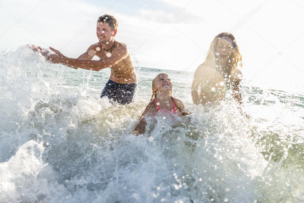 Happy family playing in the ocean