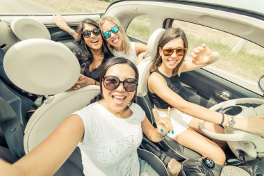 Group of girls having fun with the car