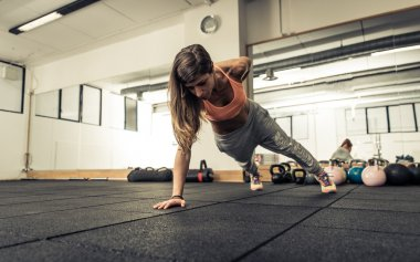 Woman making push ups on one hand