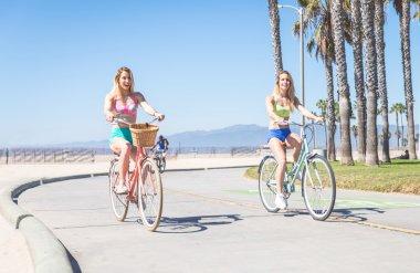 Women cycling along ocean frontwalk