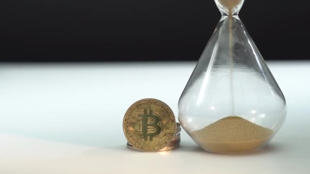 Arany Bitcoin és homokóra fehér asztalon, fekete háttérrel. Makró lövés. Az idő pénz. Homok hullik a fenékre. A jövő blokklánc-technológiája.