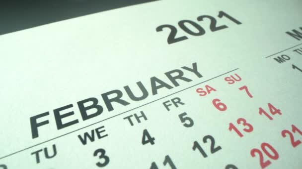 New calendar 2021 year. February and March in macro with dates and weekends marked. Macro shot with panorama. White calendar in the table