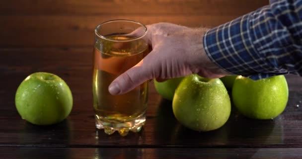 Mans kézzel veszi a poharat almaszósszal az asztalról. Vannak friss zöld almák.