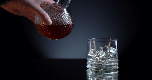 Glas Whisky mit Eiswürfel. Alkohol fließt aus der Flasche ins Glas. Schottisch auf den Felsen. Schieber schoss. Dunkel, rustikal, Hintergrund