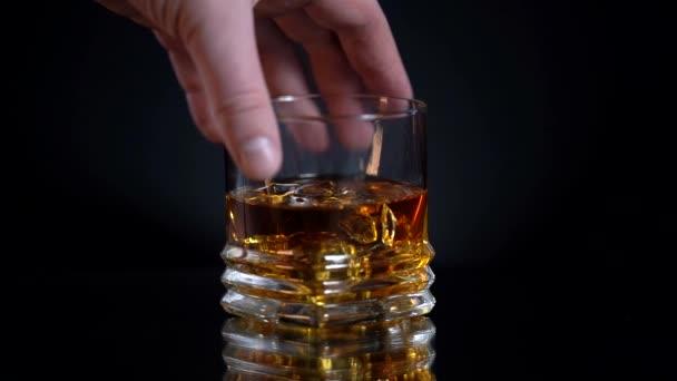 Glas Whisky mit Eiswürfel. Alkohol im Glas aus der Flasche. Schottisch auf den Felsen. Mann nimmt am Freitagabend nach anstrengender Woche Glas. Dunkel, rustikal, Hintergrund.
